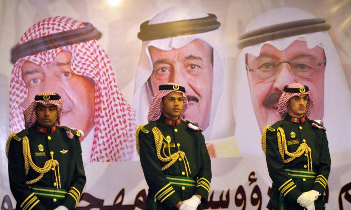 A file photo of Saudi royal guards on duty in front of portraits of former King Abdullah bin Abdulaziz (R), new King Salman bin Abdulaziz (C), and former Crown Prince Muqrin bin Abdulaziz (L) in Riyadh, Saudi Arabia. (Fayez Nureldine/AP)