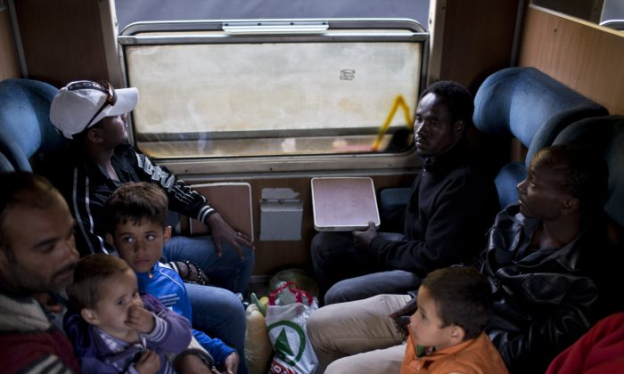 Migrants sit in a compartment of a passenger train in Presevo, close to the Serbian border with Macedonia, 300 kilometers southeast of Belgrade, Serbia. As Hungary ponders building a 4-meter (13-foot) high fence on its 175-kilometer (109-mile) border with Serbia to keep the migrants away, refugees insist that they have no other choice but to move on. (AP/Marko Drobnjakovic)
