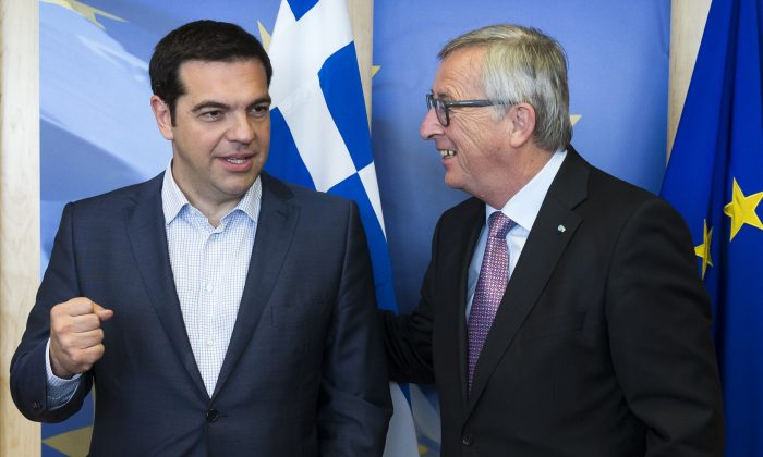Greek Prime Minister Alexis Tsipras (L) is greeted by European Commission President Jean-Claude Juncker prior to a meeting at EU headquarters in Brussels on Wednesday, June 24, 2015. (Julien Warnand/Pool Photo via AP)