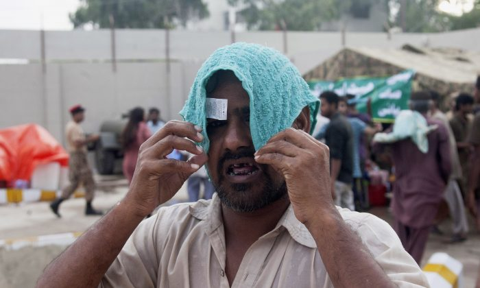 A man covers his head with a wet towel to avoid heatstroke in Karachi, Pakistan, on June 24, 2015. (Shakil Adil/AP Photo)