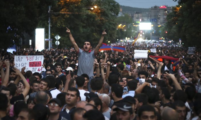 An Armenian protester shouts anti-government slogans during a protest rally against a hike in electricity prices in Yerevan, Armenia, Wednesday, June 24, 2015. (Hrant Khachatryan/PAN Photo via AP)