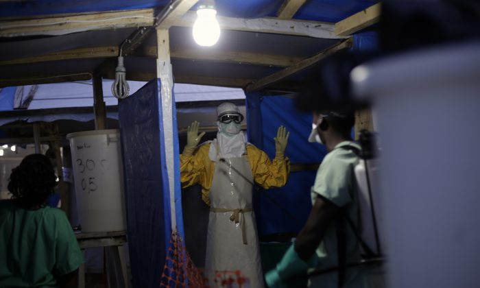 An MSF Ebola heath worker is sprayed as he leaves the contaminated zone at the Ebola treatment centre in Gueckedou, Guinea. Malaria likely killed many more people than Ebola in Guinea during last year's biggest-ever outbreak, as experts suspect many people with potential symptoms of the mosquito-spread disease stayed away from health clinics, afraid they might catch Ebola instead, a new study suggests. (AP/Jerome Delay)