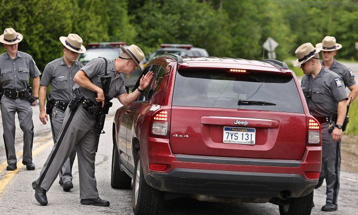 New York State Trooper Steven J. Gill searches a vehicle in Malone, N.Y., Tuesday, June 23, 2015, while searching for two prison escapees from Clinton Correctional Facility. Police began focusing intensely on an area 20 miles west of the prison that inmates David Sweat and Richard Matt escaped from prison on June 6. (Jason Hunter/The Watertown Daily Times via AP)