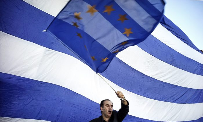 A man waves a EU flag as pro-Euro protesters take part in a rally in front of the Parliament on June 22.  2015 in Athens, Greece. (Milos Bicanski/Getty Images)