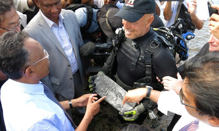 Underwater explorer Barry Clifford, right, presents a silver bar he believes is part of the treasure of the pirate Captain Kidd, to the president of Madagascar, Hery Rajaonarimampianina, left, on Sainte Marie Island, Madagascar. (AP/Martin Vogl)