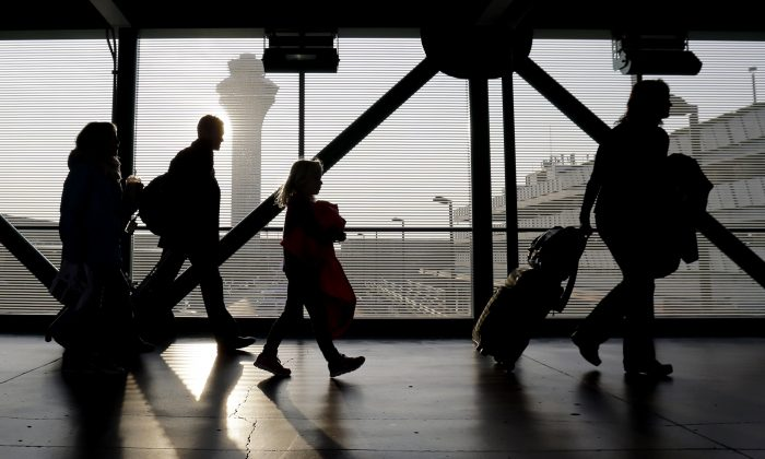 FILE - In this Dec. 1, 2013 file photo, travelers walk through terminal 3 at O'Hare International airport in Chicago. (AP Photo/Nam Y. Huh, File)