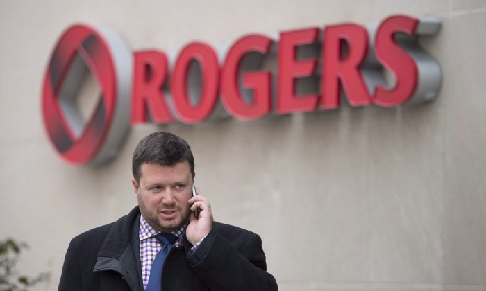 A man speaks on a mobile phone outside the Rogers Communications Inc.'s annual general meeting of shareholders in Toronto on April 22, 2014. An Ontario court's approval for Rogers to buy Mobilicity is expected to trigger a series of transactions that affects wireless customers in three provinces. (The Canadian Press/Darren Calabrese)