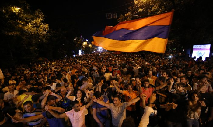 Armenian protesters dance while waving a national flag during a protest rally against a hike in electricity prices in Yerevan, Armenia, Wednesday, June 24, 2015. (Hrant Khachatryan/PAN Photo via AP)
