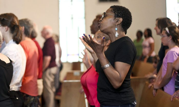 People attend a service in remembrance of the nine people killed in Charleston, S.C., Wednesday, June 24, 2015, at the African Methodist Episcopal Church in Kalamazoo, Mich. (Daytona Niles/Kalamazoo Gazette-MLive Media Group via AP)