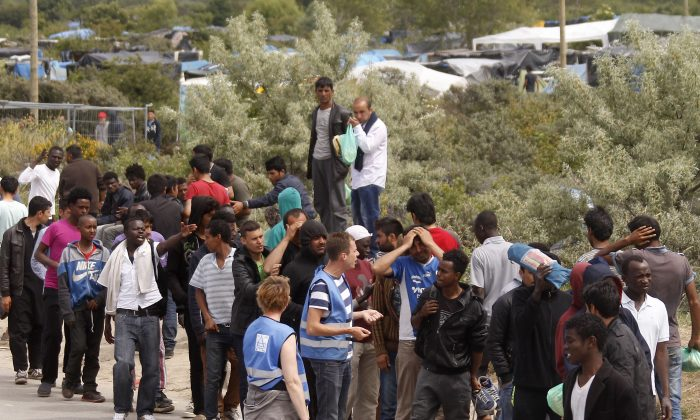"Migrants queue to receive their daily food distribution in a makeshift camp known as the ""jungle"", in Calais, northern France, Thursday, June 25, 2015. (AP Photo/Michel Spingler)"