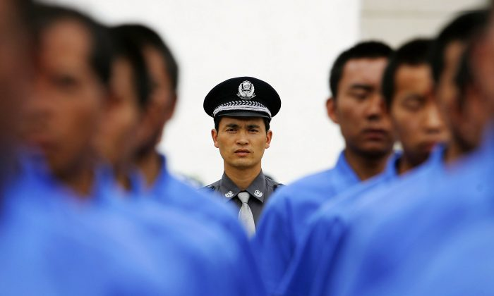 Chinese policeman (C) instructs drug rehab patients to practice marching in a compound at the Kunming Municipal Compulsory Rehabilitation Center on July 8, 2005 in Kunming, Yunnan Province, China.  (Guang Niu/Getty Images)
