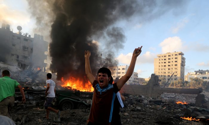 In this July 24, 2014 photo, a Palestinian shouts in an area damaged in an Israeli airstrike in Gaza City,  Gaza Strip. (AP Photo/Hatem Moussa)