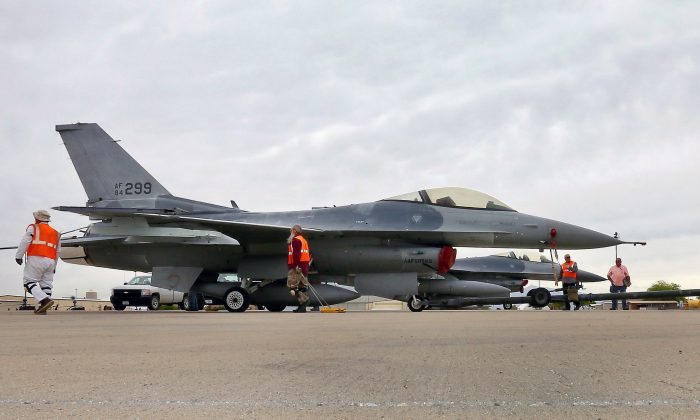 In this May 15, 2015, file photo, a boneyard crew tows an F-16 Fighting Falcon aircraft prior to the preservation process after its arrival at the 309th Aerospace Maintenance and Regeneration Group at Davis-Monthan Air Force Base in Tucson, Ariz. (AP Photo/Matt York)