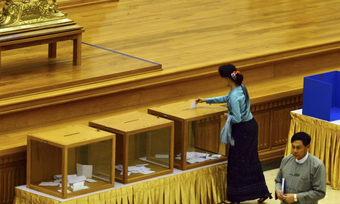 Burma's opposition leader Aung San Suu Kyi casts her vote for constitution amendments during a regular session at the Union Parliament, in Naypyitaw, Burma, on June 25, 2015. (Aung Shine Oo/AP)