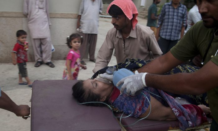 People rush a woman to a hospital as she suffered from a heatstroke in Karachi, Pakistan, on June 24, 2015. (AP Photo/Shakil Adil)