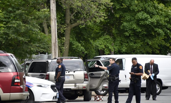 Suffolk County Police investigate the SUV car where three people were shot to death inside a car and a fourth person was injured on Davidson Street on Thursday, June 4, 2015 in Wyandanch, N.Y. (AP Photo/Kathy Kmonicek)