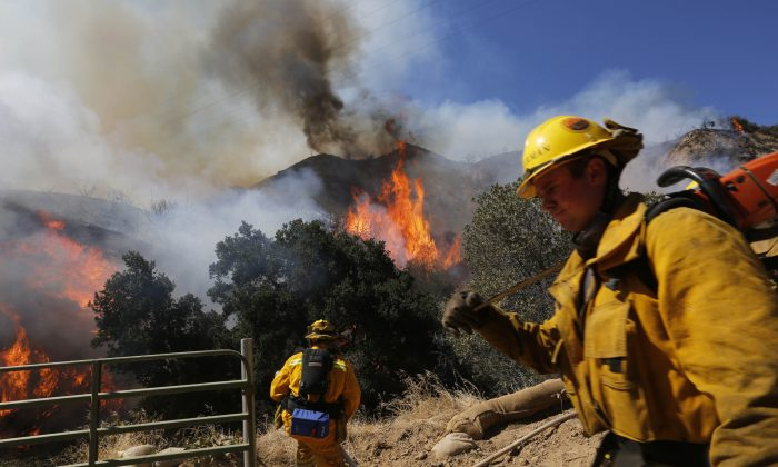 Firefighters work a ridge off of The Old Road in the Newhall Pass, Calif., in an attempt to halt the advice of a brush fire Firefighters battle a brush fire Wednesday, June 24, 2015. (Michael Robinson Chavez/Los Angeles Times via AP)