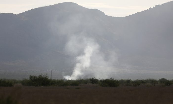 Smoke rises Thursday, June 25, 2015, from the site where an F-16 Fighting Falcon crashed Wednesday evening near Douglas, Ariz. (Mamta Popat/Arizona Daily Star via AP)