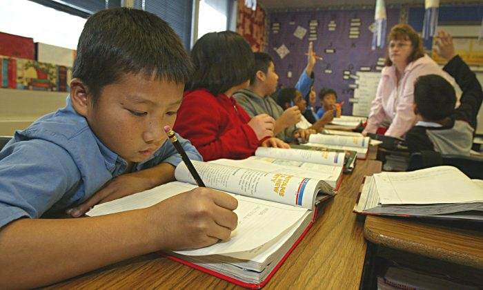 Seng Vang, age 11, practices his writing in his 5th grade class at the Herndon and Barstow Elementary school December 10, 2004 in Fresno, California. (Paula Bronstein/Getty Images)