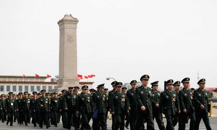 Delegates from Chinese People's Liberation Army attend the second plenary session of China's parliament on March 8 in Beijing, China. The Chinese regime is shifting its military focus to cyber and space. (Lintao Zhang/Getty Images)
