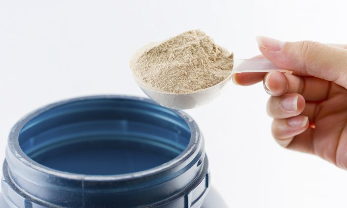 A hand weighs out protein powder. (