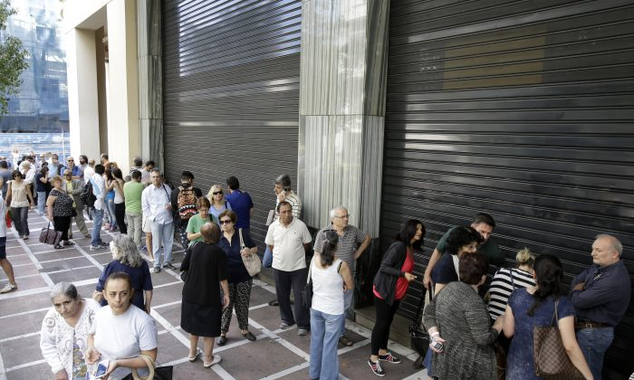 People stand in a queue outside a bank which operates on Saturday but eventually didn't open, in central Athens, on June 27, 2015. (AP Photo/Thanassis Stavrakis)