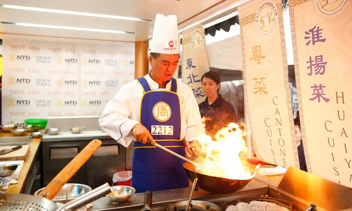 Jiguang Zhang fires up his wok during the Northeastern Cuisine portion of the New Tang Dynasty Television's 7th Annual International Chinese Culinary Competition. The competition is part of the Taste Asia Food Fest held at Times Square in New York City on June 26 and 27, 2015. (Larry Dye/Epoch Times)