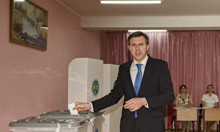 Dorin Chirtoaca, the pro-European candidate for mayor of the Moldovan capital casts his ballot in a runoff for local elections in Chisinau, Moldova, Sunday, June 28, 2015. Moldovans were voting Sunday in local election runoffs that are being seen as a test of whether the former Soviet republic moves closer to the European Union or Russia. (AP Photo/Dan Morar)