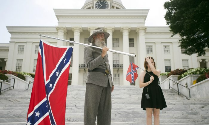 In this Saturday, June 27, 2015 file photo, Dan Williams, 65, of Ashville, Ala., holds a Confederate flag while standing with his daughter Bonnie-Blue Williams, 15, in front of the Alabama State Capitol building during a Confederate flag rally in Montgomery, Ala. ((Albert Cesare/The Montgomery Advertiser via AP)
