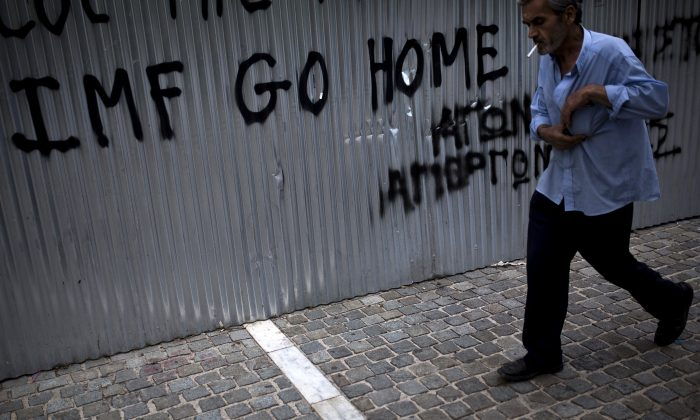 """A man walks in front of a graffiti reading """"IMF Go Home"""" in Athens, Greece, on June 27, 2015. (Angelos Tzortzinis/AFP/Getty Images)"""