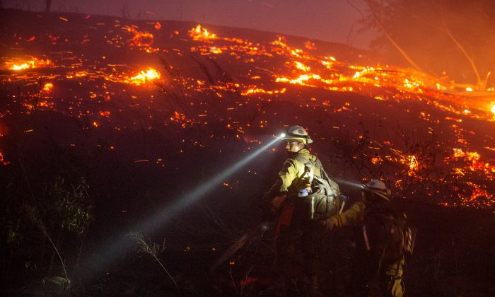 In this Sunday, June 28, 2015 photo provided by The Wenatchee World, U.S. Forest Service firefighters from Leavenworth cut brush near houses in northern Wenatchee, Wash. (Don Seabrook/The Wenatchee World via AP)