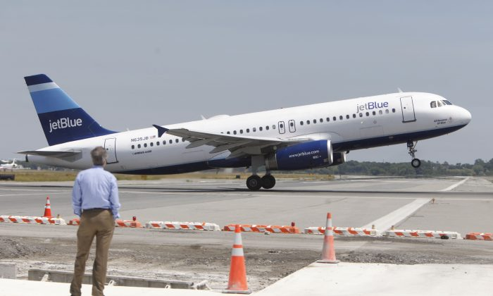 A man watches a JetBlue airplane take off from John F. Kennedy International Airport, on June 2, 2010. (Seth Wenig/AP Photo)