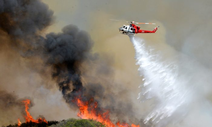 A Los Angeles City Fire helicopter drops water on flames, Wednesday, June 24, 2015, in Santa Clarita, Calif. (AP Photo/Rick McClure)