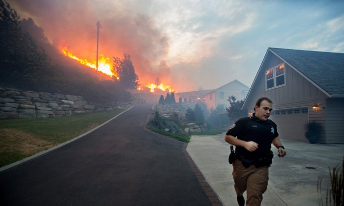 A Chelan County Sheriff's deputy races to check that all residents have left their home as flames approach houses at Quail Hollow Lane in Wenatchee, Wash. (Don Seabrook/The Wenatchee World via AP)