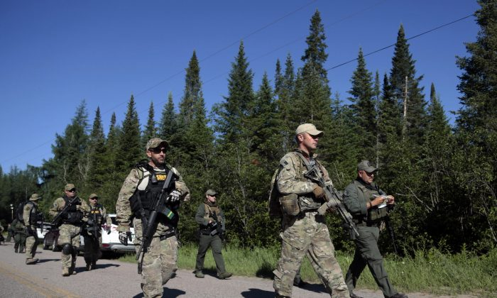 In this Wednesday, June 24, 2015 photo, Law enforcement officers walk along a road before going into the woods near Mountain View, N.Y. (AP Photo/Mike Grol)