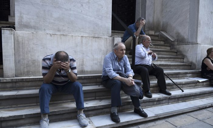 Elderly people, who usually get their pensions at the end of the month, wait outside a closed bank in the northern Greek port city of Thessaloniki, Monday, June 29, 2015. (AP Photo/Giannis Papanikos)