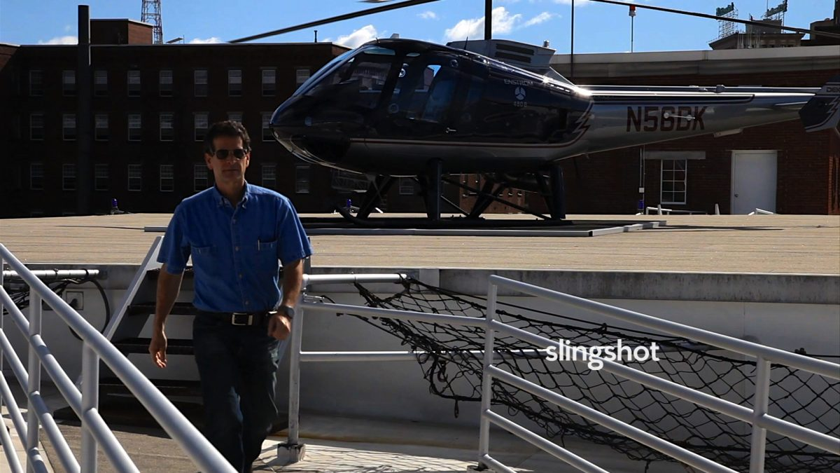 man in front of helicopter in Slingshot