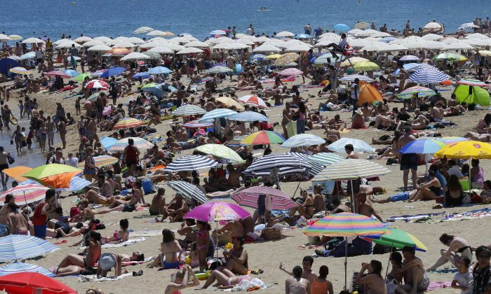 People sunbathe on a beach in Barcelona, Spain, Sunday, June 28, 2015. (AP Photo/Manu Fernandez)