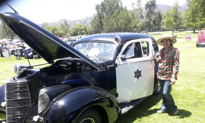 A visitor poses at an exhibit of a 1938 Studebaker Commander police car at the 43rd annual Los Angeles Police-Celebrity Golf tournament, held on June 20. (Timothy Wahl)