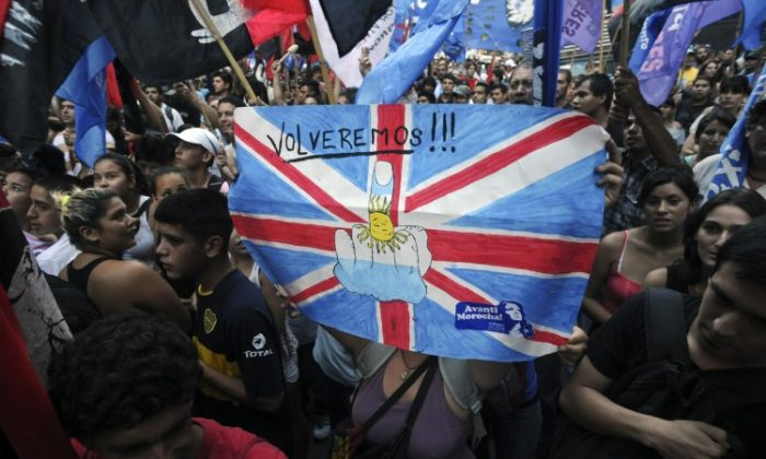 Argentine activists hold a poster reading 'We will be back!' as they take part in a demonstration in front of the British embassy in Buenos Aires on January 24, 2012. (Sergio Goya/AFP/Getty Images)