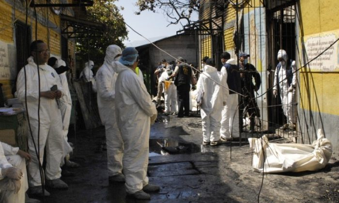 Forensic personnel remove the charred remains of inmates at the National Prison compound in Comayagua, Honduras, on February 15, 2012. (Orlando Sierra/AFP/Getty Images)