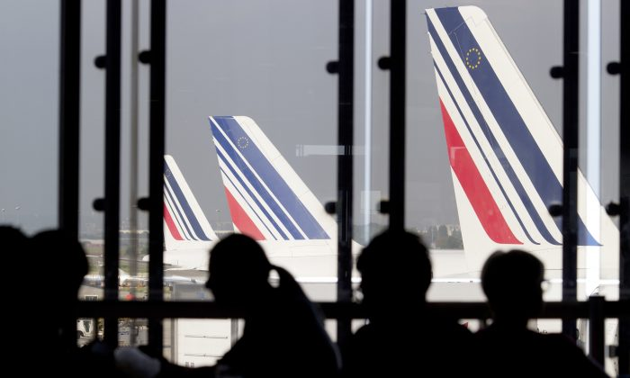 Passengers wait in a lounge as Air France planes are seen behind at Paris-Orly airport on Sept. 15, 2014. (Kenzo Tribouillard/AFP/Getty Images)