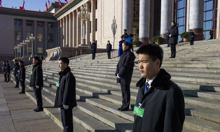 Chinese security guards stand outside a meeting of the National People's Congress in Beijing on March 10. The Chinese regime passed a new national security law that undermines foreign businesses. (Fred Dufour/AFP/Getty Images)
