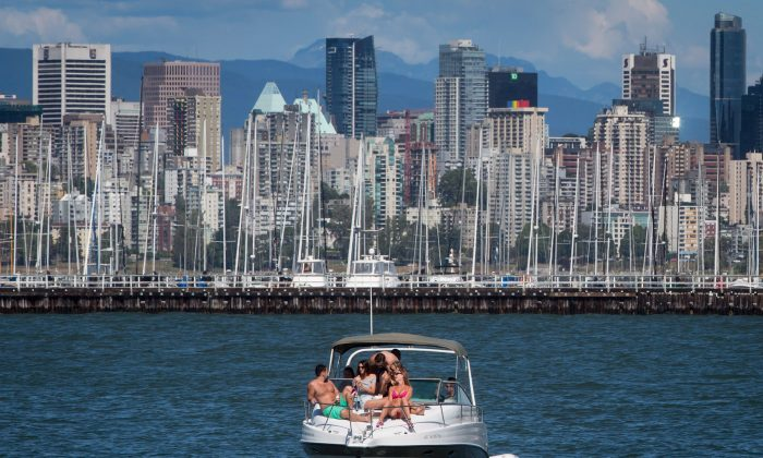 People relax on a boat off Jericho Beach in Vancouver on June 13, 2015. Nearly half of Canadians will dip into their savings or take on debt as they look to make the most of the summer weather, according to a new poll. (The Canadian Press/Darryl Dyck)