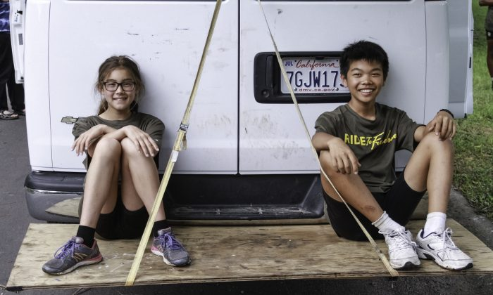 Aila Verheijke and Tanner Gao taking a break on the back of the Ride2Freedom van. (Chris Jasurek/Epoch Times)