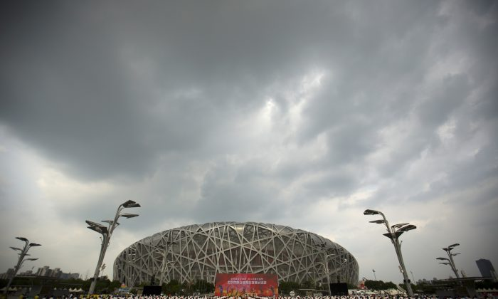 Participants dance under threatening skies at a gathering to watch the announcement of the 2022 Winter Olympics host city outside the Beijing Olympic Stadium on Friday. (AP Photo/Mark Schiefelbein)