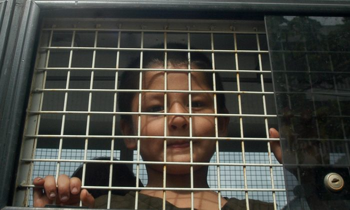 An ethnic Uighur Muslim boy stands inside a police van in Thailand's southern Songkhla Province on March 15, 2014. Thailand officials said they suspected a group of 200 people recently rescued from a human trafficking camp were ethnic Uighur Muslims, as calls mounted from the international community to protect the group and ensure they are not forced back to China. (AP Photo/Sumeth Panpetch)