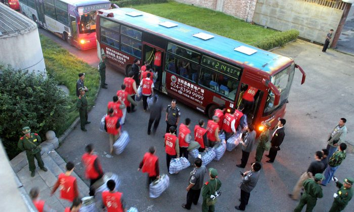 Chinese prisoners board a bus under guard as they move to a newly constructed prison in Shenyang in northeastern China's Liaoning province on Aug. 20, 2005. (AFP/AFP/Getty Images)