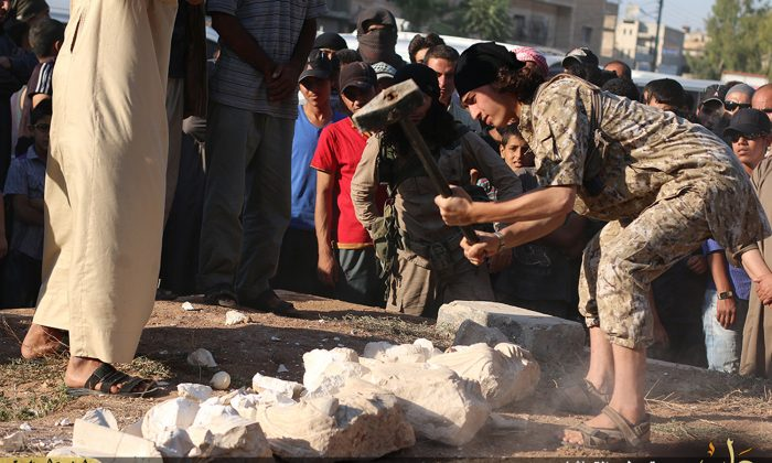 In this image posted on a militant website by the Aleppo branch of the Islamic State group on Friday, July 3, 2015, which has been verified and is consistent with other AP reporting, a militant smashes items that the group claims are smuggled archaeological pieces from the historic central town of Palmyra, Syria. (Militant website via AP)
