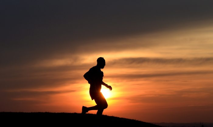 A jogger runs during the sunset after a warm spring day on March 16, 2015, in the Olympic park in Munich, southern Germany. Meteorologists forecast temperatures around 15 degrees and further sun in the region. AFP PHOTO/CHRISTOF STACHE        (Photo credit should read CHRISTOF STACHE/AFP/Getty Images)